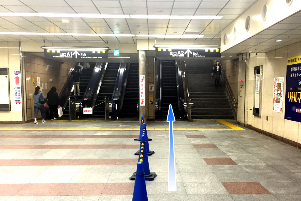 向かって右側のエスカレーターを登り、A2出口より地上へ